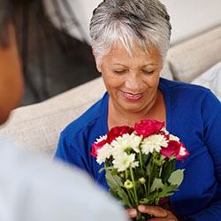 Older female holding a bouquet of flowers