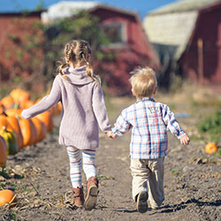Two small children in a pumpkin patch