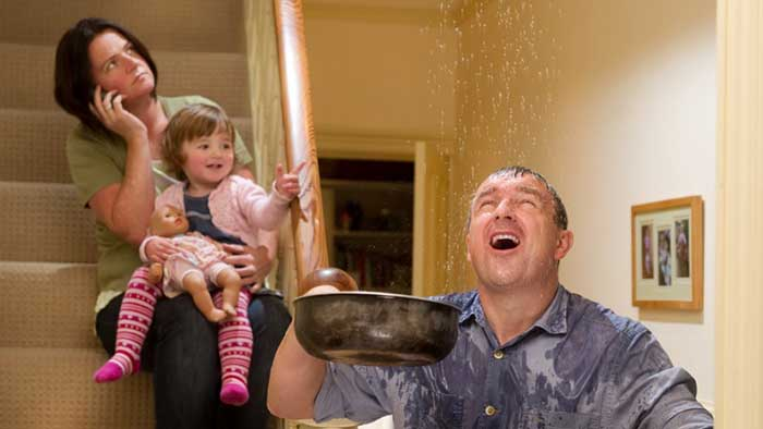 man with family holding a pan to catch water from leaky roof Insurance