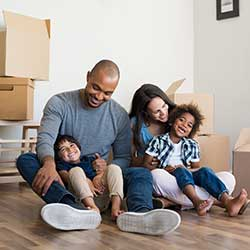 Family with boxes sitting on floor of new home Consumer Loan
